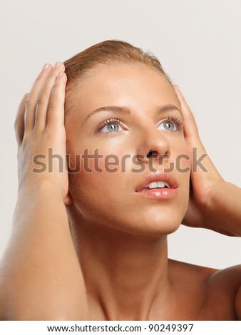 closeup beauty portrait of beautiful woman touching her head, looking into the light