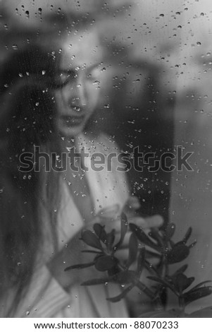 closeup beauty portrait of blonde woman blowing from behind a wet window