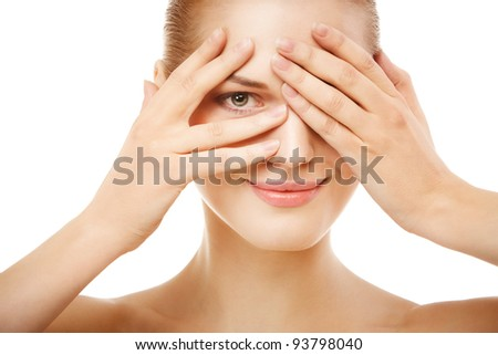 Closeup beauty portrait of young woman looking jokingly through fingers