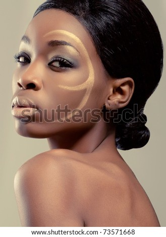 Closeup beauty shot of a young black woman with golden makeup