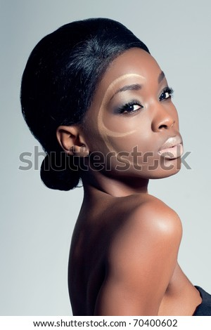 Closeup beauty shot of a young woman with golden makeup