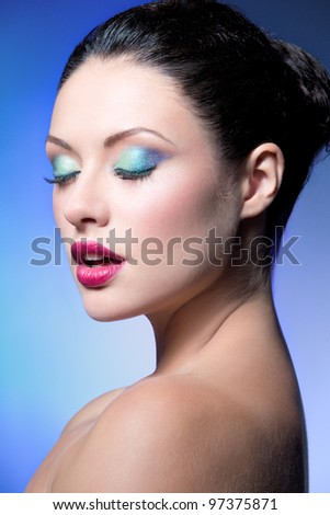 closeup beauty shot of young caucasian brunette: red lips and blue green eyeshadows