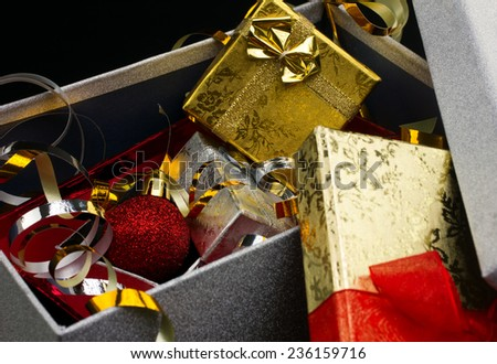 closeup big opened glamour gift box with bright little gift boxes and christmas red ball