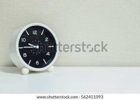 Closeup black and white alarm clock for decorate in a quarter to ten or 9:45 a.m. on white wood desk and cream wallpaper textured background with copy space