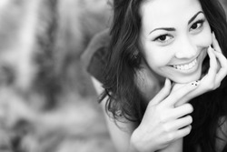 Closeup black and white portrait of a happy young woman smiling
