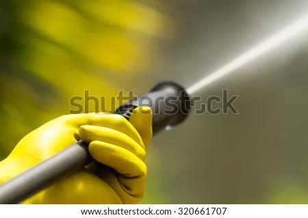 Closeup black head of high pressure water cleaner as waterbeam emerges.