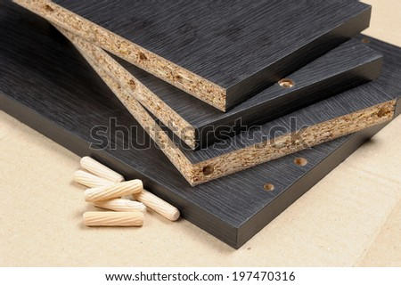 closeup black particleboard and bolt