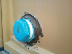 Closeup - Blue PVC Pipe Stopper Plastic plugs for closing drainage holes On the dirty brown background of the temporary bathroom