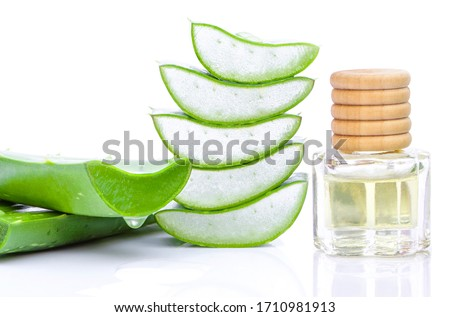 Closeup bottle of Aloe Vera essential oil extract with Aloe Vera leaf and cut slice isolated on white background. Skincare, health, beauty and spa concept.
