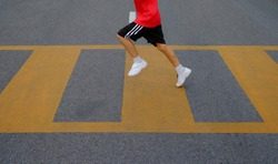 closeup boy's leg running on crosswalk