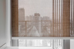 Closeup brown color Roller blinds curtains. sunlight through the windows in the city. Selective focus image.