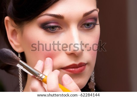 closeup brunette young lady bride get ready for the event by makeup artist