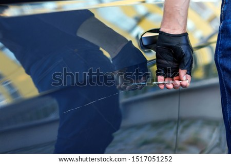 Closeup bully hands in black gloves are scratching automobile with nail, pin. Bandit is spoiling appearance of private car. Man is making scratch on auto without signaling. Vandalism act concept. Foto stock ©
