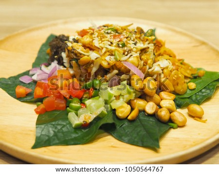 Closeup Burmese Tea Leaf Salad or Lahpet in a wooden plate with Wild Betel Leaves on a light wooden table in warm tone
