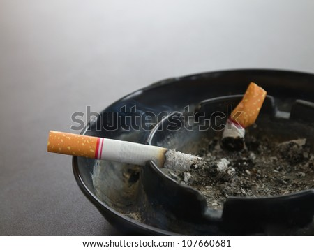 Closeup burning cigarette in ashtray and smoke on the table