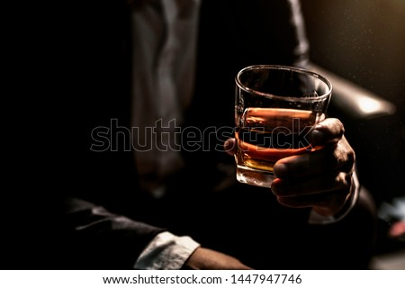 Closeup businessmen holding a glass of whiskey