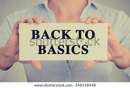 Closeup businesswoman hands holding white card sign note with back to basics text message isolated on grey wall office background. Retro instagram style image