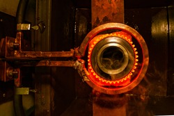 closeup calcining hot metal steel gear parts in a factory induction furnace with smoke and flame