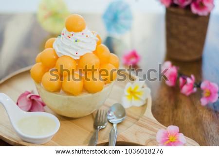 Closeup cantaloupe Bingsu on tray, Bingsu or Bingsoo, Korean shaved ice dessert with sweet toppings and fruit and varieties with ingredients,  popular dessert.