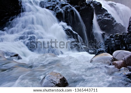 Closeup capture of a side view  featuring gushing water at a high flow rate cascading over the bedrock edges and boulders downstream disappearing into a crevice along the wet surface of granite rocks
