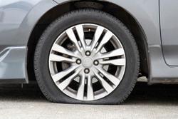 Closeup car flat tire on the road.