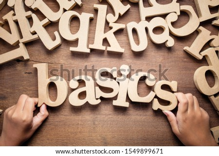 Closeup child's hand arrange wooden alphabets on the table as Basics word