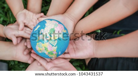 Closeup children hands holding earth ( blur ) over green grass background. World harmony green peace environment spring and earth day together concept.