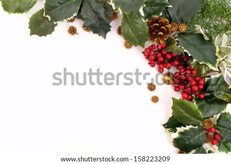 Closeup christmas decoration arrangement with holly, berries and pine cones