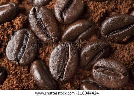 Closeup coffee beans at roasted coffee heap. Coffee bean on macro ground coffee background. Arabic roasting coffee - ingredient of hot beverage.