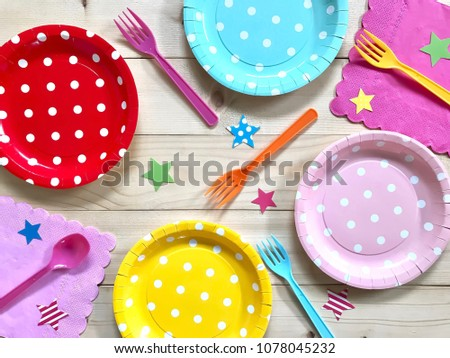 Closeup colorful polka dot paper plate,plastic fork & spoon,napkin with star on wooden background.The concept of Birthday party accessories,decoration,picnic utensil.Top view.Selective focus.