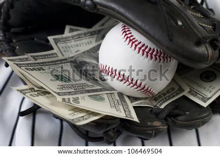 Closeup concept of baseball and money. Focus is on baseball.