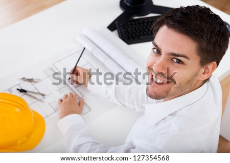 Closeup cropped image of a young male architect working on blueprints spread out on a table