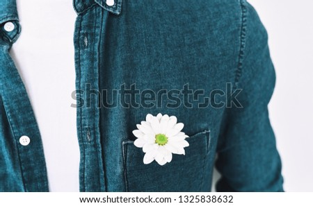 Closeup cropped image of handsome man in blue shirt with a flower in pocket, posing over white wall. Valentine's Day. Mother's Day concept