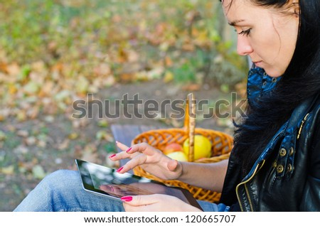 Closeup cropped portrait of a young girl sitting outdoors on a garden bench using her tablet