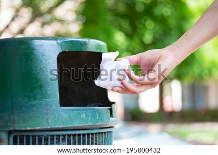 Closeup cropped portrait of someone tossing crumpled piece of paper in trash can, isolated outdoors green trees background
