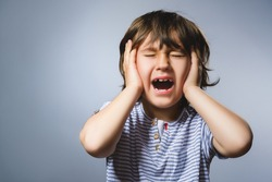 Closeup crying boy with worried stressed expression on gray background
