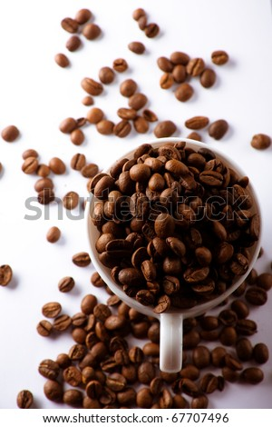 Closeup cup filled with coffee beans, coffee beans are also scattered around. White background.