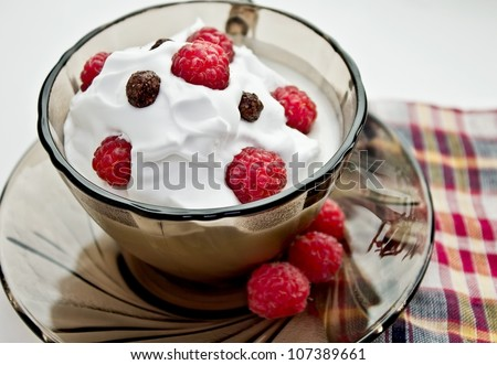 Closeup cup of dessert with ice-cream, whipped cream, raspberry and chocolate balls