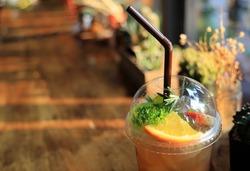 Closeup cups of fresh ice  Apple tea with orange slice, strawberry, kiwi, rosemary on wooden table.