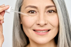 Closeup cut portrait of senior mature older Asian woman touching clean face eye contour with antiaging pipette serum essence oil looking at camera. Anti wrinkle prevention skin care products concept.
