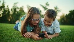 Closeup cute boy and girl lying on green grass in meadow with cellphone. Portrait of brother and sister using smartphone in park. Happy children looking at mobile phone screen outside