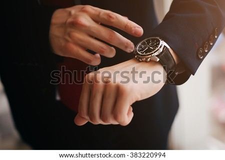 Photo of  closeup designer watch on businessman hand, he looks on the time and hurrying