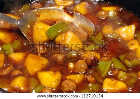 Closeup detail of a pan of sweet and sour chicken with pineapple, green pepper, and spices cooking, with some thin wisps of steam visible