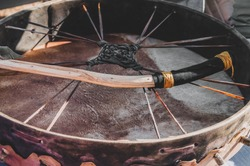 Closeup detail of a shamanic spiritual meditation ritual drum with a natural handmade wild wood branch drumstick  for a shamanism ceremony- Concept of mystical paganism or alternative lifestyle