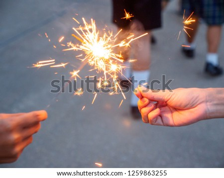Closeup detail of a sparkler being lit by another sparkler during the Loy Krathong Festival. Pathum Thani, Thailand. Travel and holidays. #1259863255
