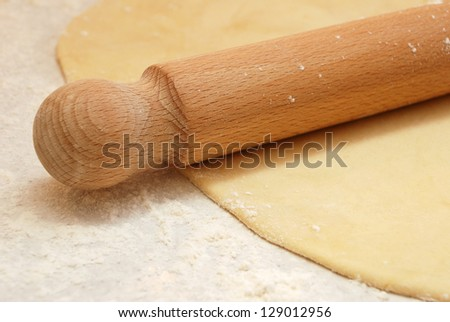 Closeup detail of a wooden rolling pin on thinly rolled out fresh pastry