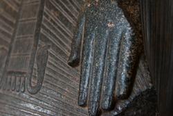 Closeup detail of black granite pharaoh statue, fingers.