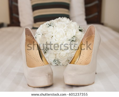 Closeup detail of bridal high heeled platform stiletto wedding shoes with flower bouquet #601237355