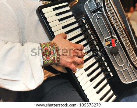 Closeup detail of hands playing a black accordion instrument.