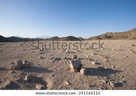 Closeup detail of stony desolate arid desert landscape with mountains